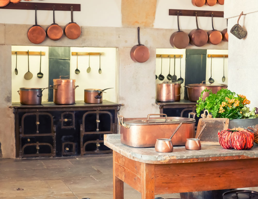 Copper pots and pans on the walls of an Edwardian style kitchen